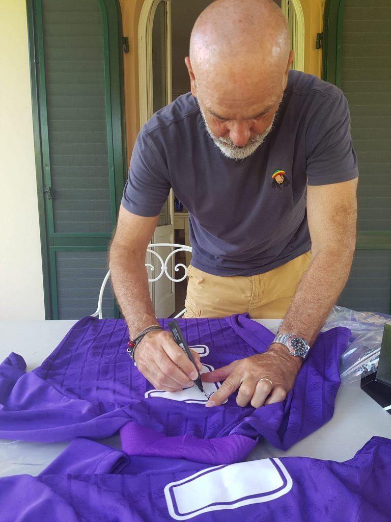 Stefano Pioli mentre firma la maglia messa all'asta